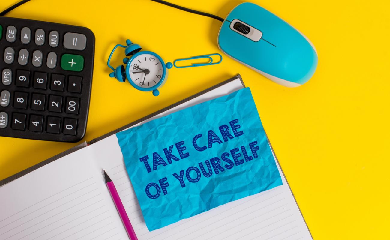 Yellow desk with a calculator, clock, notepad, pencil, PC mouse, and a blue note with take care of yourself written on it.